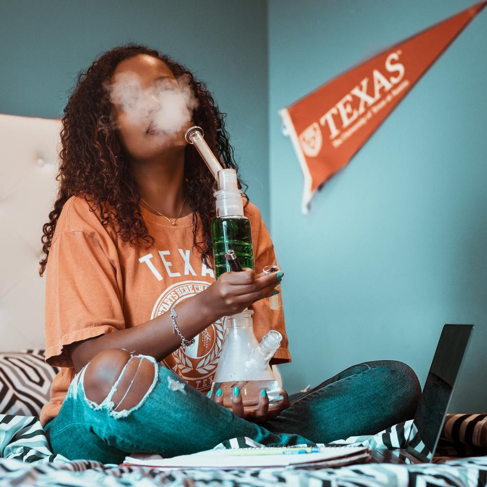 College student smoke a bong on their bed