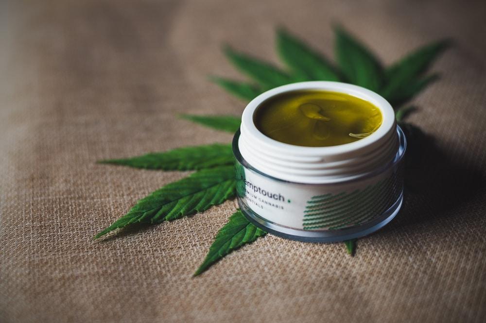 Tub of CBD infused topical cream on a hemp leaf