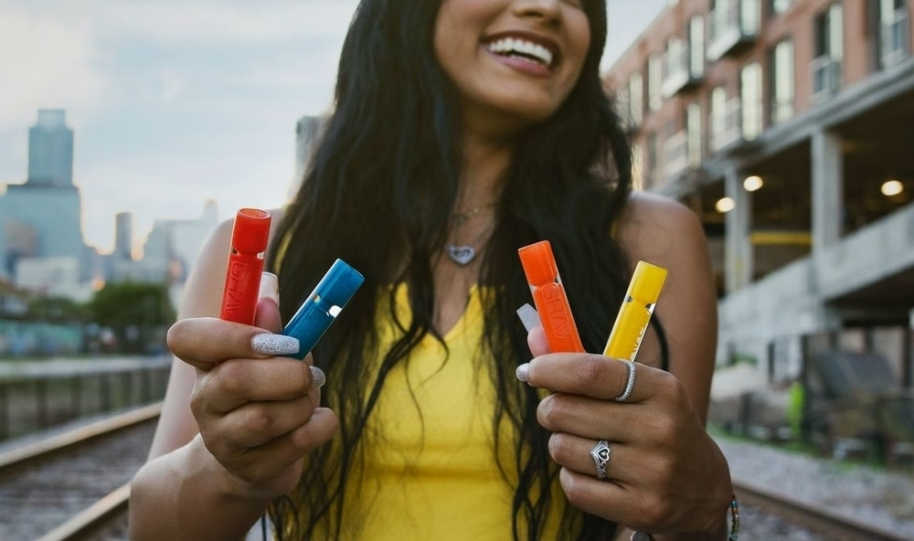 Smiling person in a yellow shirt holding several colourful smoking pipes